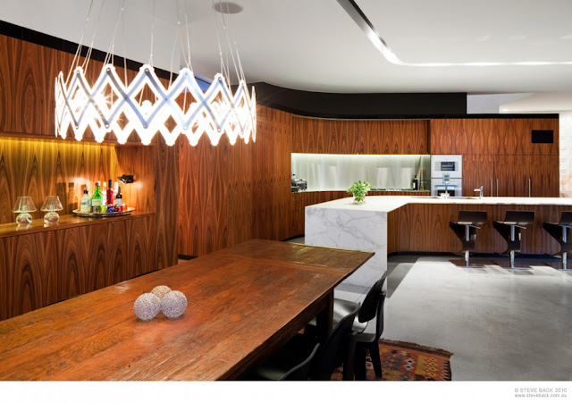 Dining room and the kitchen of River House by MCK Architects