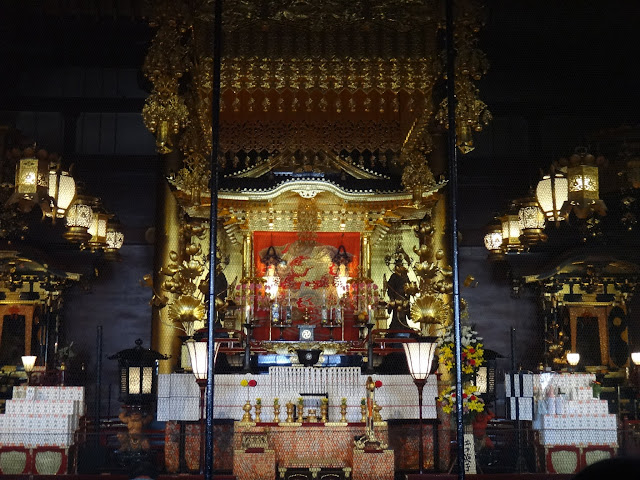 The visitors bow and pray in front of the Asakusa Shrine at the main temple's hall of Asakusa Sensoji Kannon Temple in Tokyo, Japan