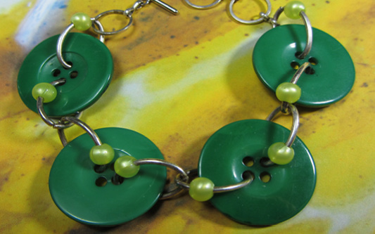 Bold bracelet has big green buttons accented with small shiny beads connected with silver chain loops
