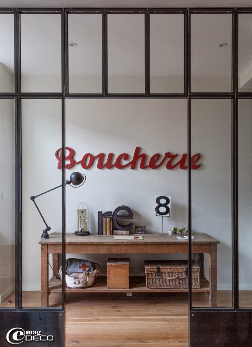 Chez Isabelle de 'Bazar & Co Store', derrière une verrière, une grande table de drapier chinée chez 'Marie & Benoît' à Saint-Martin-de-Ré, lampe Jieldé chinée à la réderie d'Amiens