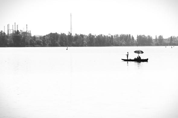 Fotografia in bianco e nero di pescatori in barca sul Lago di Mezzo a Mantova