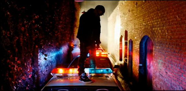 Kanye takes a minute to ogle his own reflection on the top of the cop car.