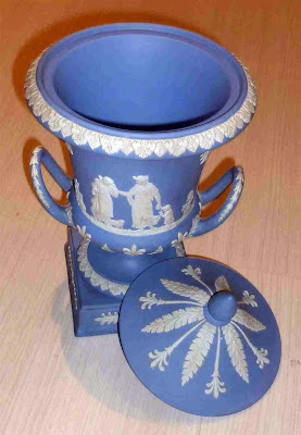 Jarrón de bizcocho ceramico, con decoración bicolor de figuras a modo cratera griega y tapa solapada.