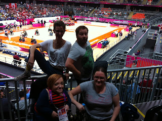 Picture of 4 people. The back row is a non-disabled woman and a non-disabled man perched on a railing. The front row is 2 women in wheelchairs. In the background wheelchair rugby players are on the court warming up.
