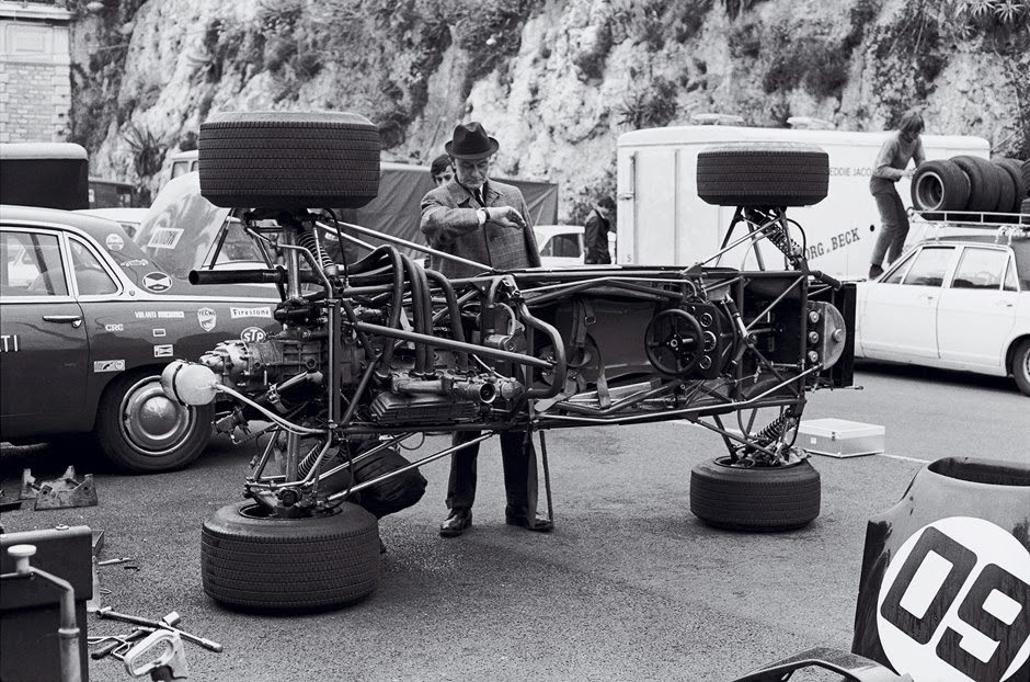 Un cotxe de F1 tombat de costat, sobre dues de les seves rodes, i així els mecànics poden treballar, la foto sembla dels 60.