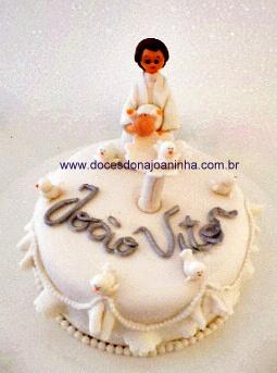 Bolo decorado batizado com padre segurando bebê sobre pia batismal, babadinhos e pombinhas