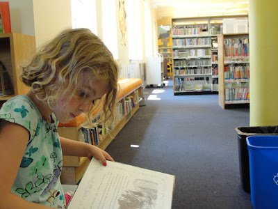 kid reading books at library