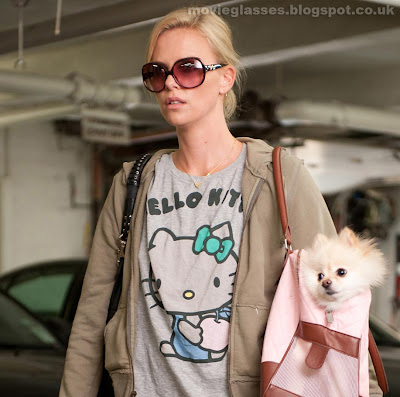 Charlize Theron in Young Adult looking rough with a dog in a bag, but wearing Dior Sunglasses so its all good