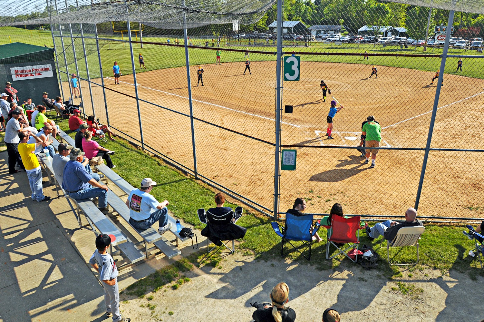 families and other spectators watch the action on the field at rucker s sports complex on opening day of the city s little league season on monday