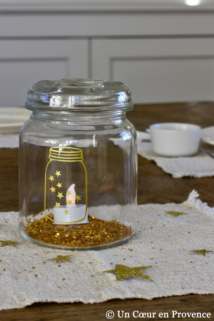 Christmas table with a jar decorated with a sticker and filled with golden stars and led candle