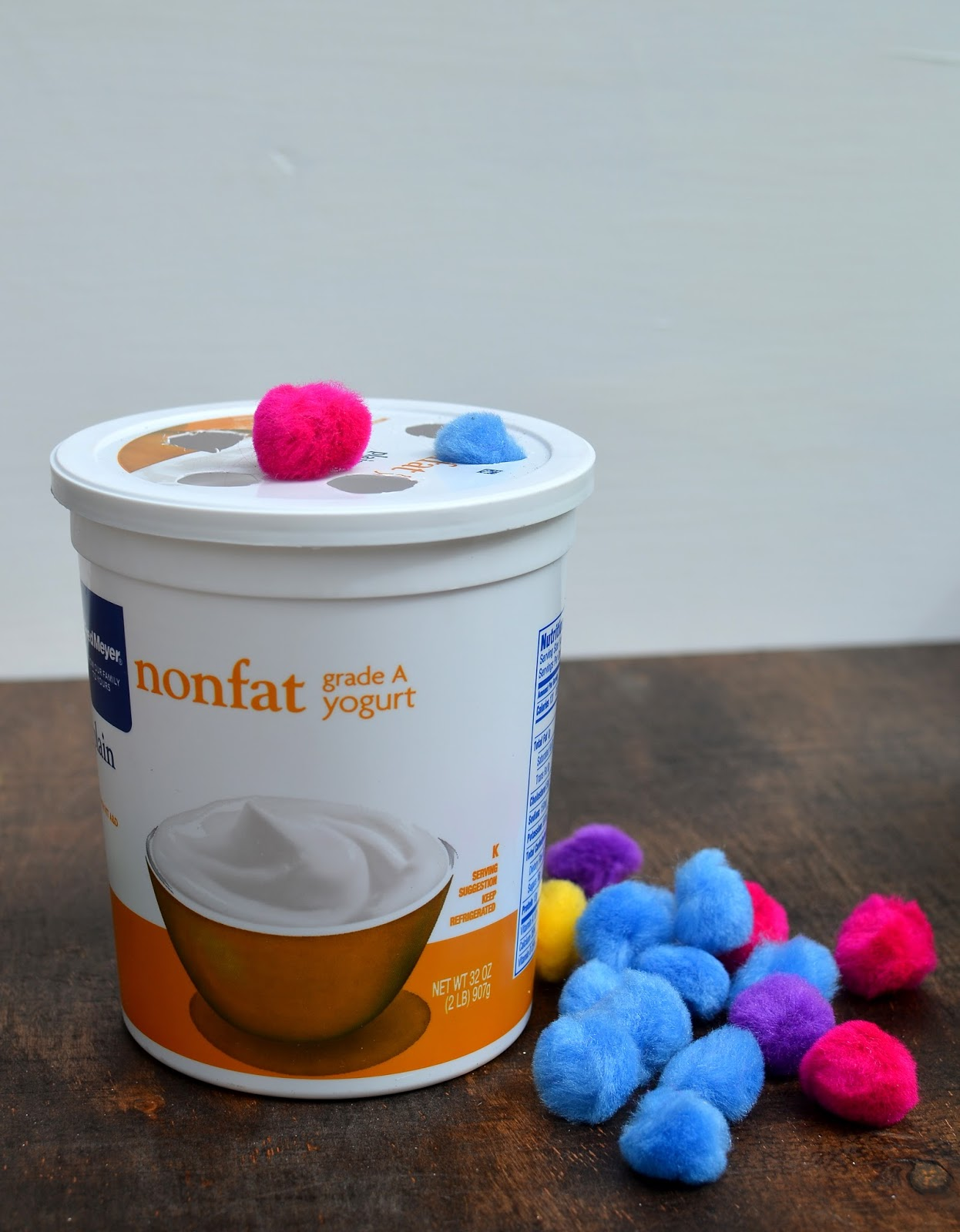 Activities for toddlers for traveling: yogurt container and fluff balls