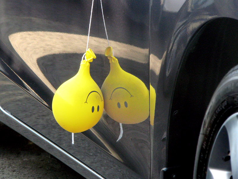 Happy Face balloon reflected in car - smile turned upside down is a frown - Not A Happy Camper