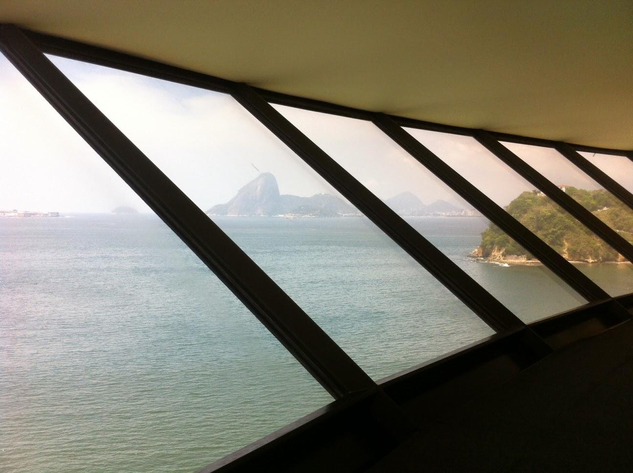 Descrição da Foto: Vista da janela de dentro do museu, elas estão lado-a-lado, em formato retangular vertical inclinadas para fora. Podemos observar do outro lado o mar, uma montanha do lado direito arborizada, no centro ao fundo o Pão de Açúcar.