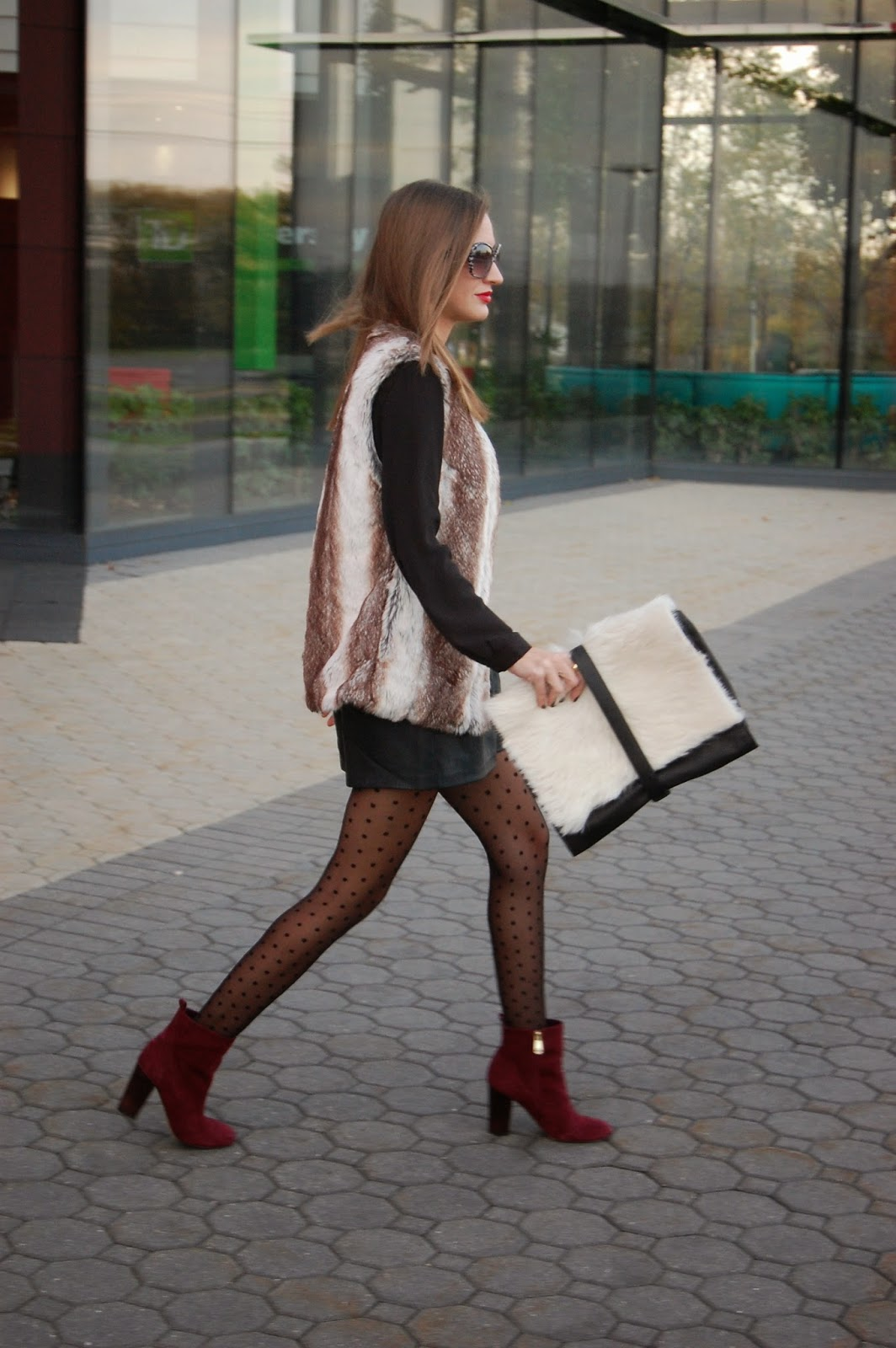 Wearing leather shorts and sheer polka dot tights, Little Liffner wild thing multi clutch