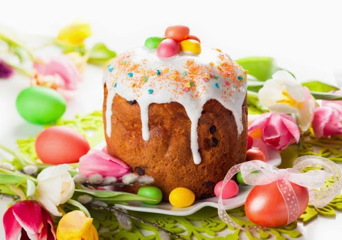 Easter cake with white frosting on top and candied eggs scattered around
