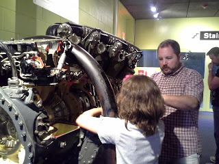 a really big engine and a father showing his daughter.