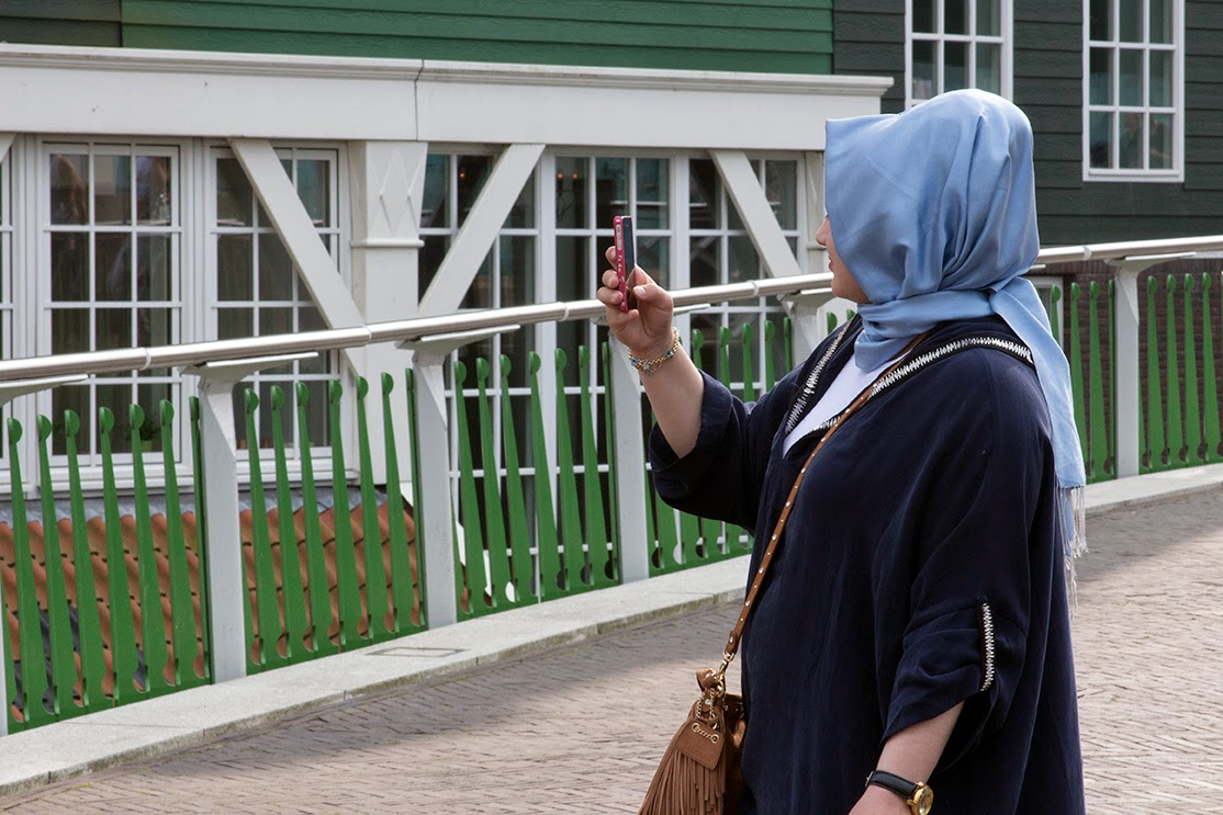 woman with blue scarf taking a photo