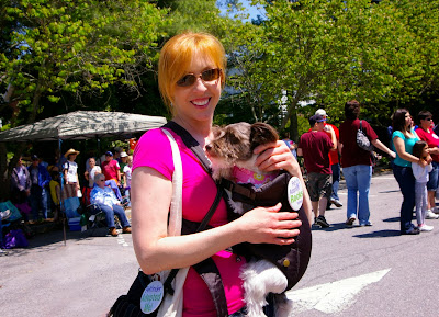 Pixel & Mommy Jenny at an outdoor festival. Pixel is being carried in a special harness on Mommy.