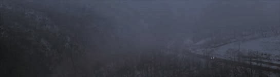 A lone vehicle's headlights can be seen travelling along a mountain road, shrouded in heavy fog.