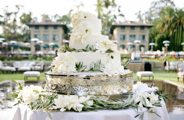 Beautiful three layer wedding cake with flowers on a mercury cake stand