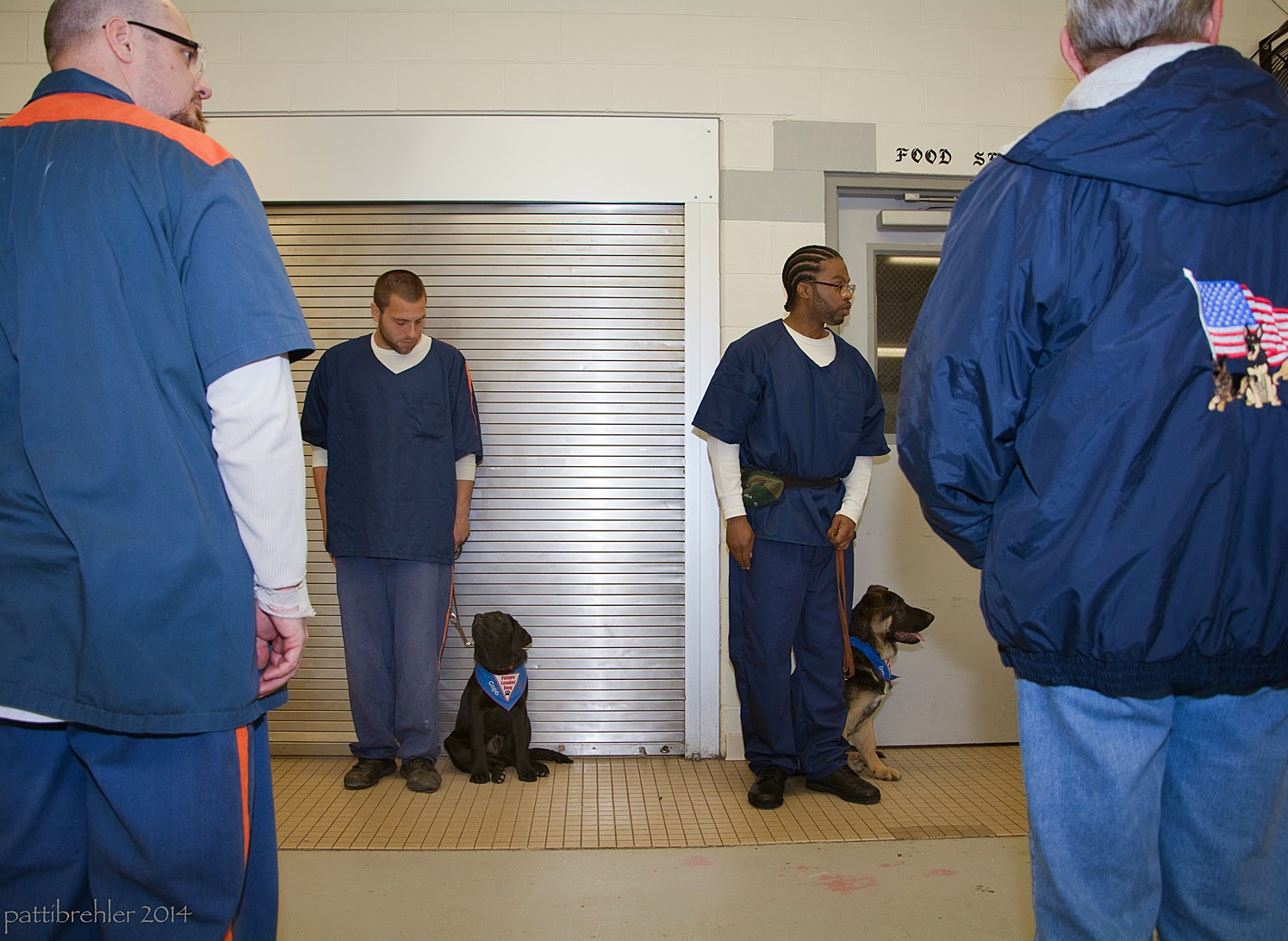 A man dressed in the blue prison uniform is standing on the far left side facing away from the camera; a woman dressed in blue jeans and a blue jacket is standing on the far right facing away from the camaer. In the distance between them are two men dressed in the blue prison uniforms, they are standing against the wall and facing the camera. The man on the left side has a small black lab puppy sitting at his left side looking up at him. The man on the right has a small german shepherd puppy sitting on the floor on his left side, but looking to the right. Both puppies are on leash and are wearing the blue Future Leader Dog bandana.