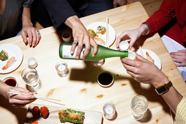 Mencelupkan bagian nasi dari sushi nigiri pada saus kecap asin