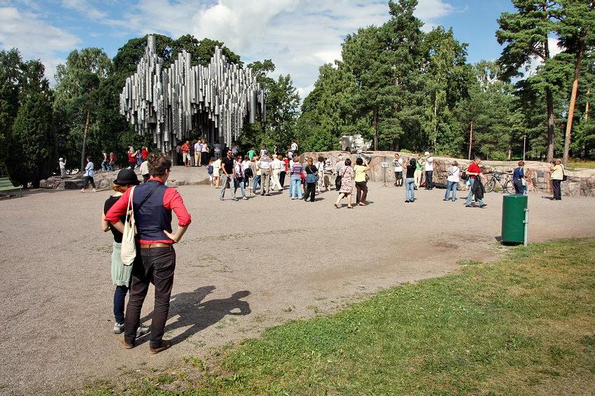 Pormenor do Parque Sibelius, no lugar onde foi erguido o Monumento, o qual, presente num plano intermédio da foto. Por detrás um conjunto de árvores e em primeiro plano um casal jovem de costas a tirar fotografias. Logo a seguir, no largo em frente do monumento, bastantes turistas em circulação