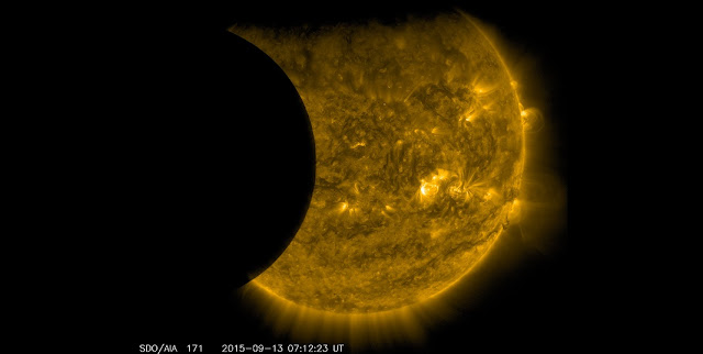 NASA's Solar Dynamics Observatory captured this image of Earth and the moon transiting the sun together on Sept. 13, 2015. The edge of Earth, visible near the top of the frame, appears fuzzy because Earth's atmosphere blocks different amounts of light at different altitudes. On the left, the moon's edge is perfectly crisp, because it has no atmosphere. This image was taken in extreme ultraviolet wavelengths of 171 angstroms. Though this light is invisible to our eyes, it is typically colorized in gold. Credits: NASA/SDO