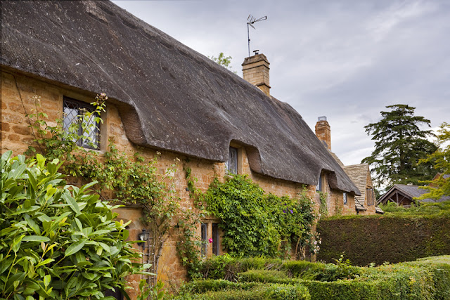 Thatched cottages made from local iron stone in Great Tew by Martyn Ferry Photography