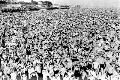 millions of white people standing on a Coney Island beach, looking up at a photographer.