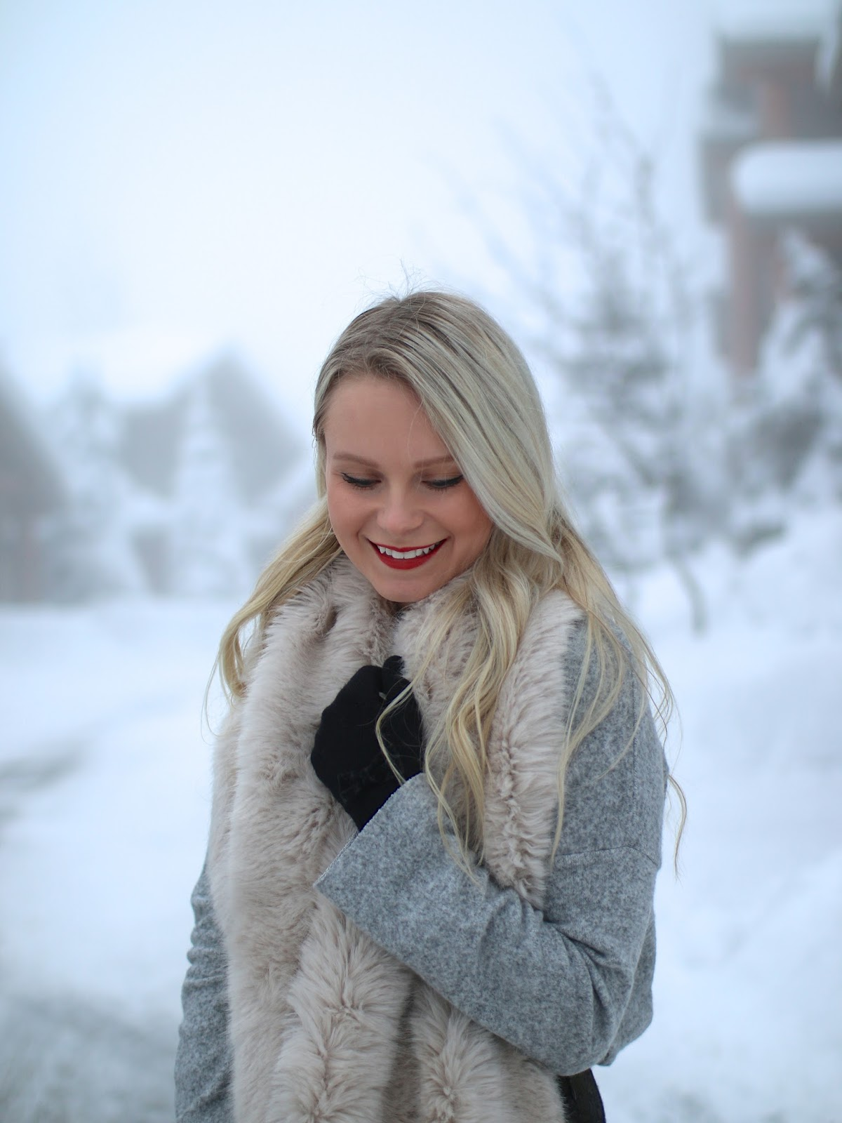 a blonde women having fun in the snow, dressed in an elegant outfit and faux fur scarf from zara