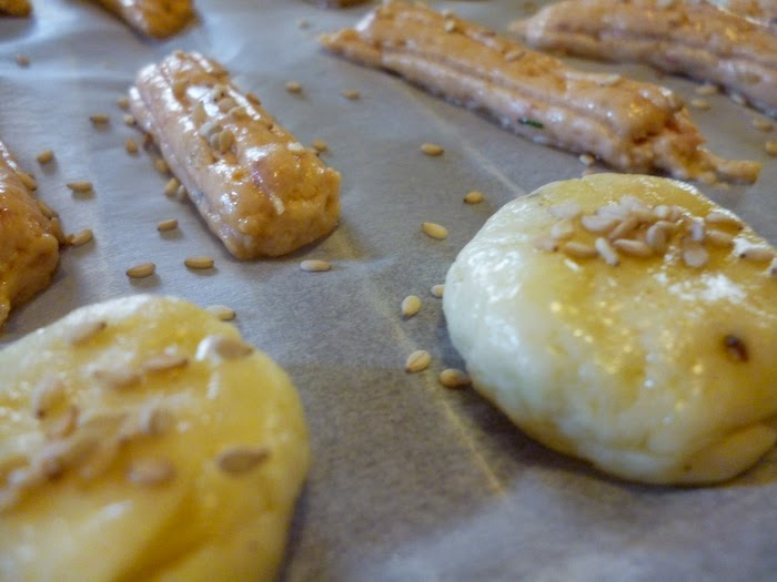 Unbaked cookies on oven paper sprinkled with sesame seeds
