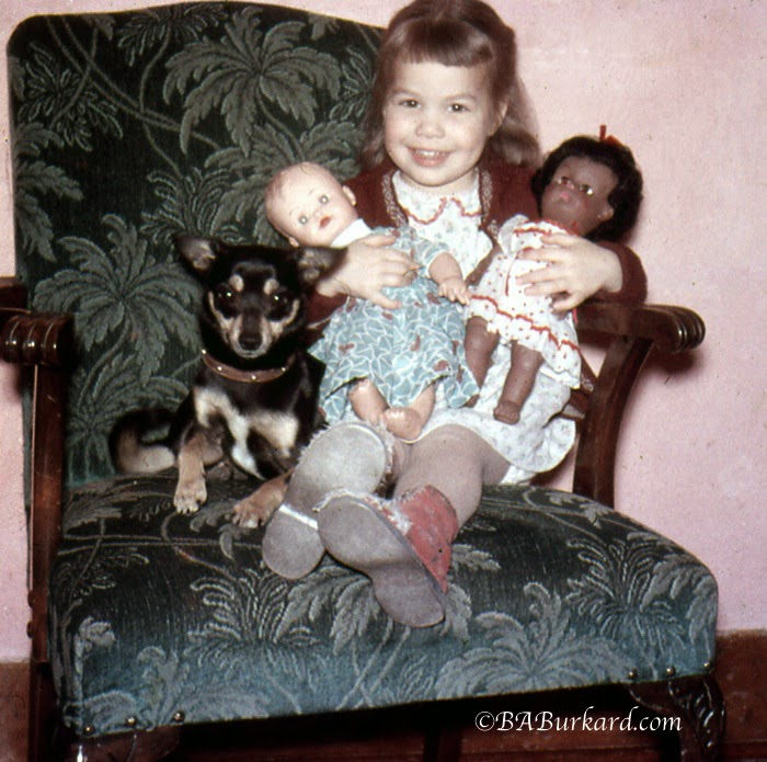 Grandma as a little girl hold dolls that her mother made cloths for