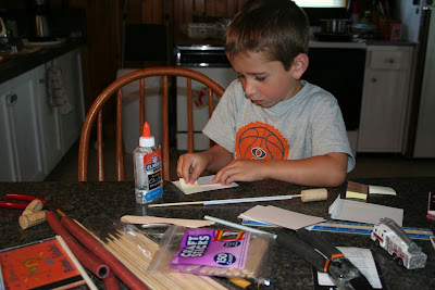 Boy constructing a Wind Turbine out of popsicle sticks, corks, and skewers: STEM mom