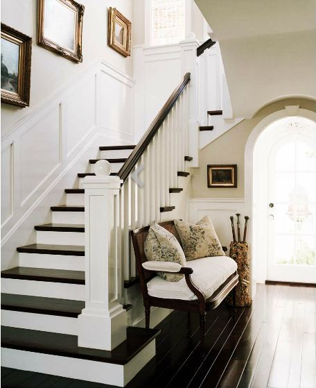 Foyer with dark wood Louis XVI bench with white cushions, dark wood floor and staircase