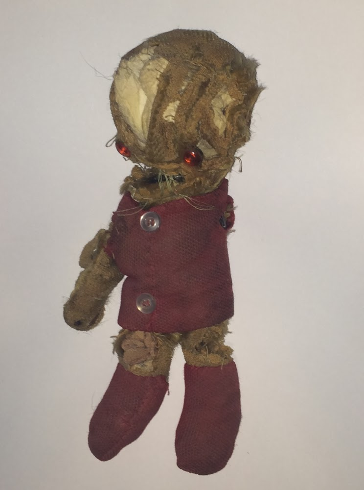 Well-worn, torn, patched old teddy bear