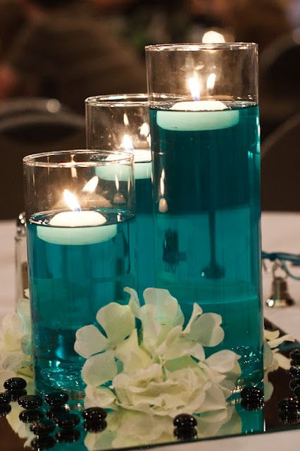 teal glass centerpiece with floating candles