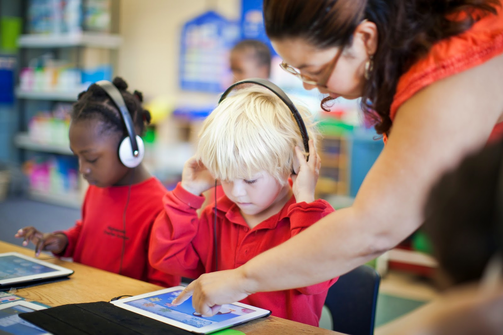 Picture of Teacher helping young student using an Ipad at their desk.