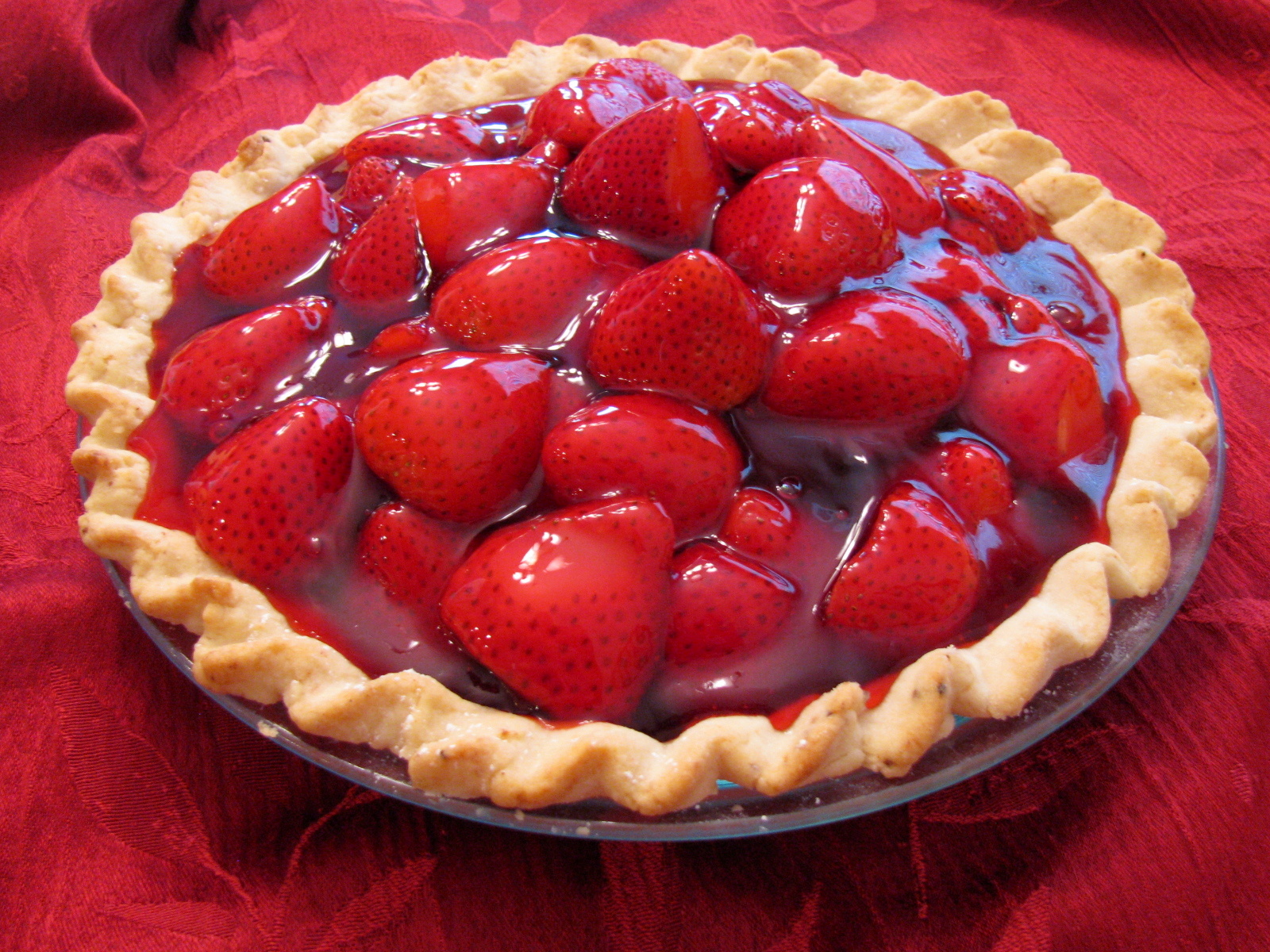 Fresh berries are combined with flour, sugar and cinnamon, piled into a prepared crust, and dotted with butter. Then on goes the top crust, and the pie is slipped into a hot oven until the filling bubbles and the crust turns a golden brown.