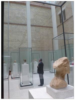 In der Ferne ein Mann im Maßanzug zwischen den Ziegelsteinwänden des Neuen Museums inmitten von Schaukästen mit Büsten darin ...