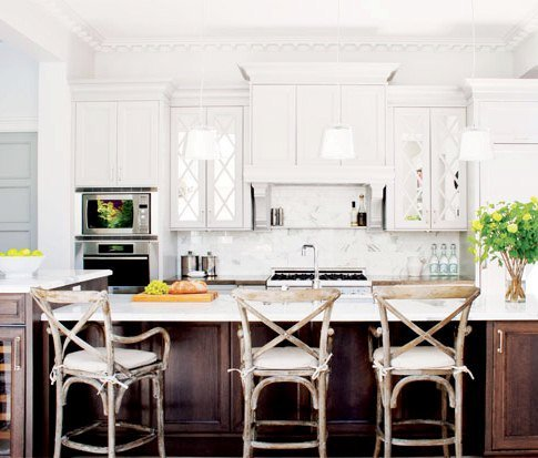 white kitchen with island with dark wood cabinets, reclaimed wood chairs and stone backsplash