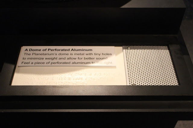 "In large print and Braille reads the following exhibit signage: ""A Dome of Perforated Aluminum.  The Planetarium's dome is metal with tiny holes to minimize weight and allow for better sound.  Feel a piece of perforated aluminum to the right.""  To the right of the text is a piece of silver aluminum with many small holes in it for visitors to feel."