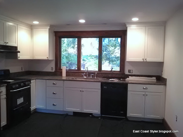 ceiling high cabinets,black appliances,granite counters,white cabinets