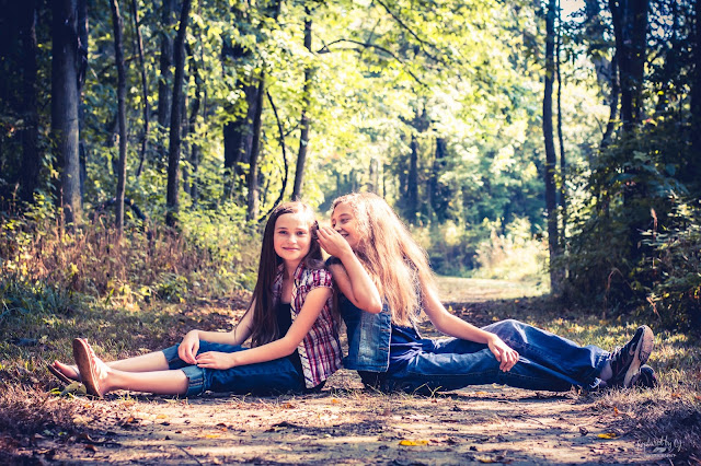 two sisters sitting back to back in the woods whispering a secret
