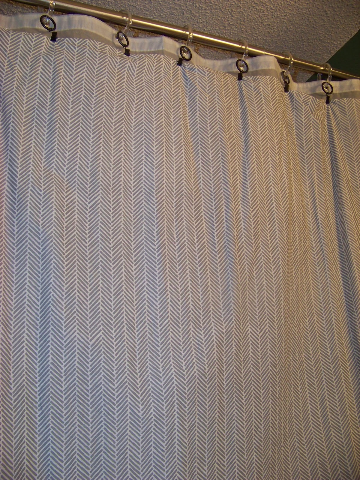 The shower curtain is a chevron herringbone top sheet from a set of