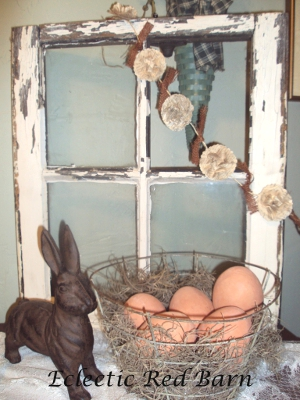Old window, cast iron bunny, wire basket filled with terracotta eggs and flower garland