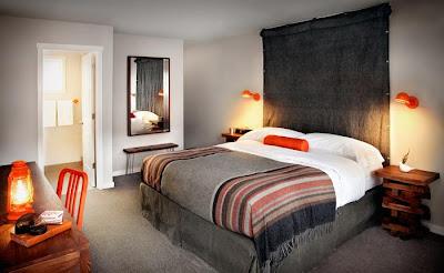 dormitorio con detalles color naranja lampara silla libros cuadros cojines