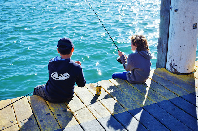Photo of two kids sitting on a jetty in Rose Bay fishing