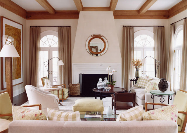 Living room with exposed beams, a white fireplace with a polished round mirror on the mantel, french doors and gingham accent pillows