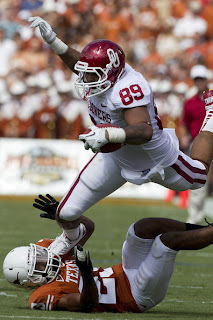 Austin Haywood #89 of the Oklahoma Sooners dives over a defender during a game against the Texas Longhorns at the Cotton Bowl on October 8, 2011 in Dallas, Texas. The Sooners defeated the Longhorns 44 to 3. (October 7, 2011 - Source: Wesley Hitt/Getty Images North America)